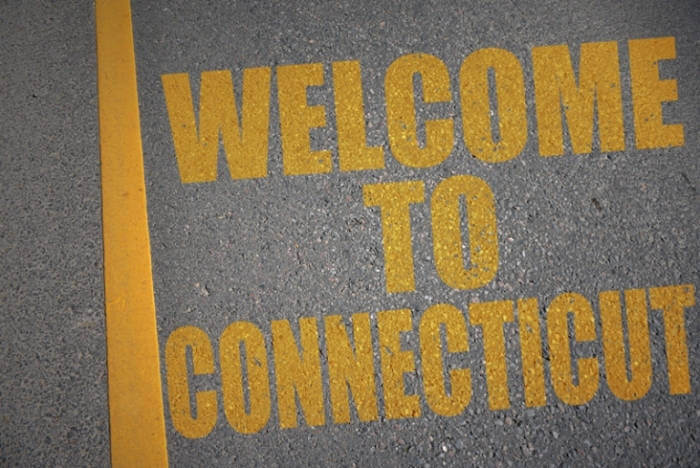 Welcome to Conneticut, written in yellow on asphalt road
