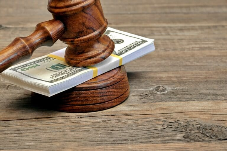 Wad of Money and Judges Gavel on Wooden Table