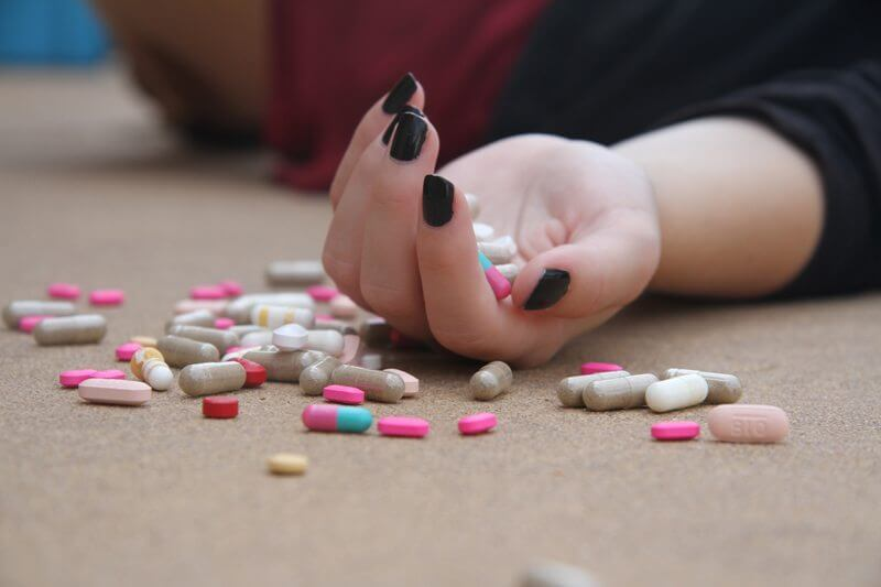 Female hand with pills in it and around
