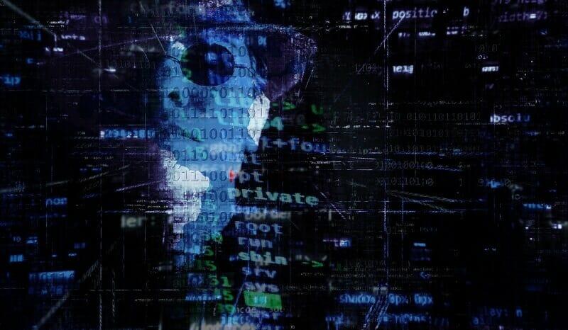 hacker's face behind computer code