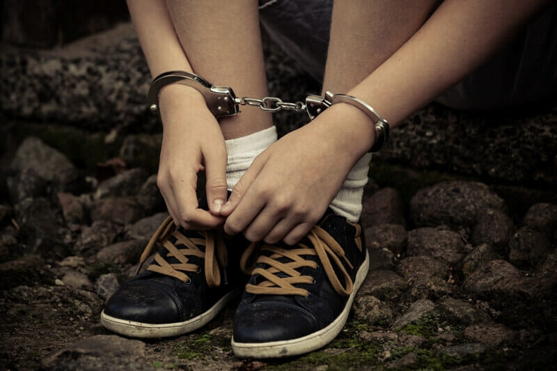 Young boy in handcuffs, only hands and foots on photo